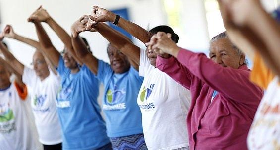 Foto de vários idosos praticando alongamento durante atividade fisica do Programa de Saúde do Idoso
