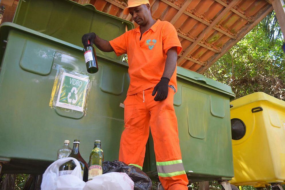 Foto de um profissional de limpeza colocando garrafas de vidro numa lixeira de coleta seletiva
