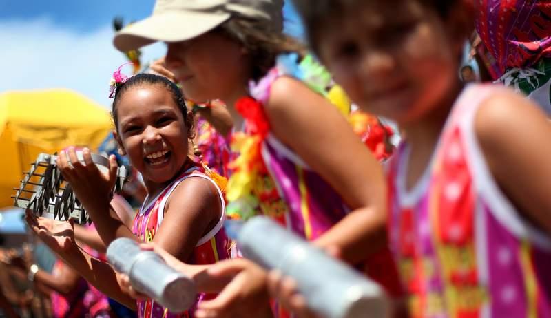 Foto de várias meninas tocando instrumentos durante a apresentação de um bloco de carnaval