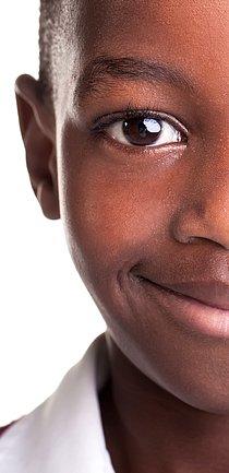Foto em close do rosto de um menino sorrindo