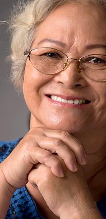 Foto em close do rosto de uma idosa sorrindo