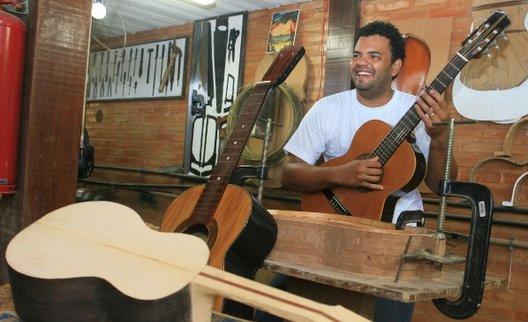 Foto de um professor da Escola Fundição de Artes e Ofícios, posando para foto com um dos violões confeccionados por ele