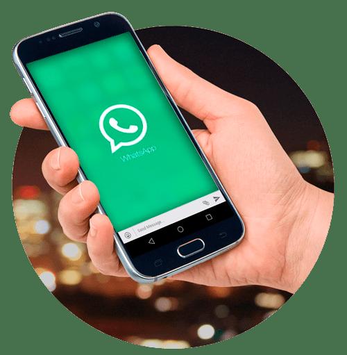 Foto de uma mão segurando um smartphone com a tela do WhatsApp aberta