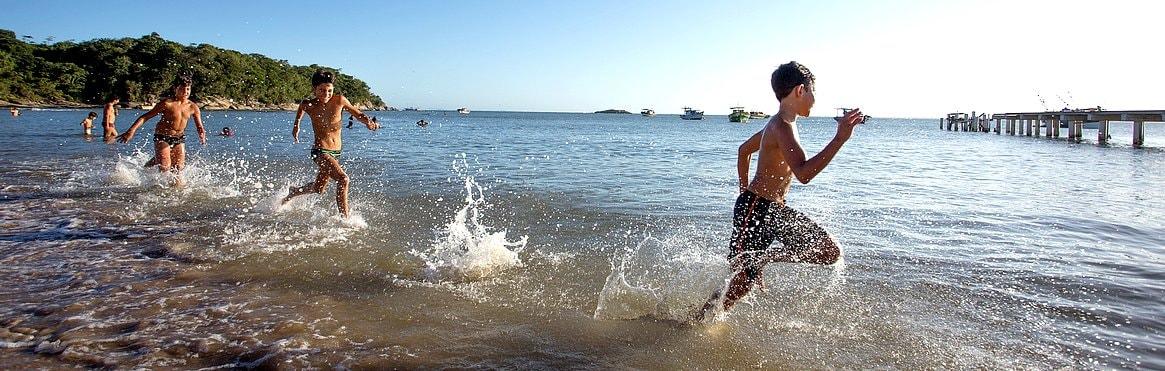 Fotos de várias crianças correndo na beira da água na praia