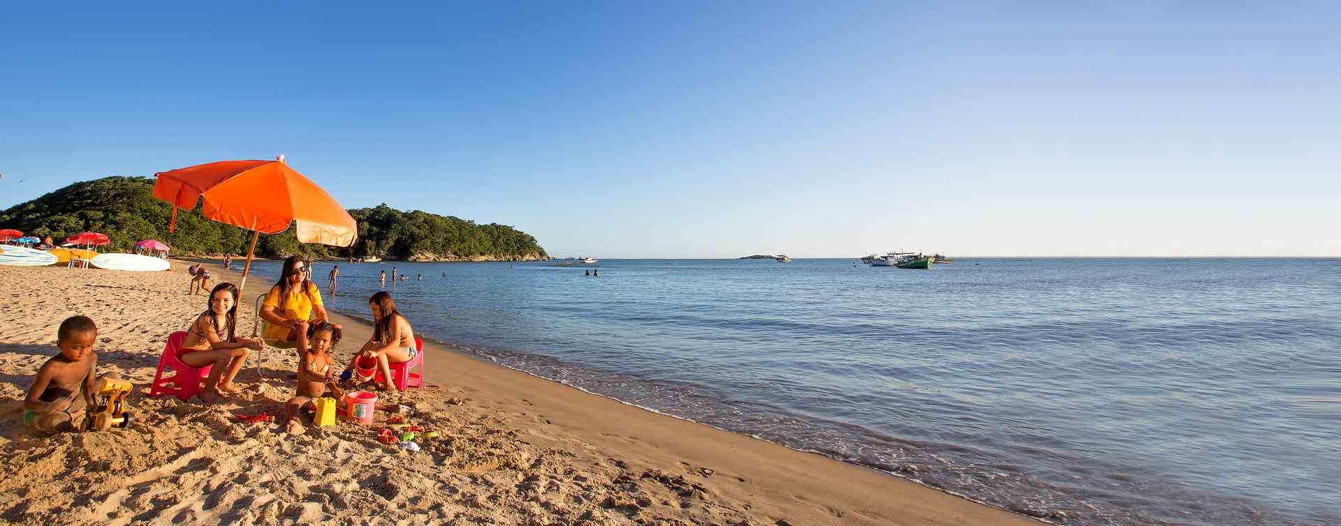 Família em um dia de sol na praia em baixo de um guarda-sol esquerda em primeiro plano, já em segundo plano outras barradas na areia, em terceiro plano pedras e vegetações. O mar a direita com algumas embarcações âncoradas