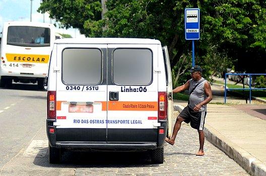 Foto de um passageiro subindo numa Van do transporte público