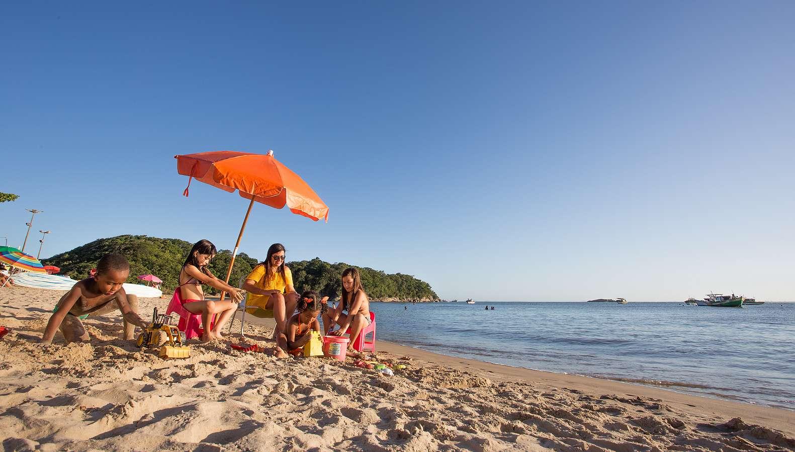 Foto de uma família curtindo a Praia Boca da Barra num dia ensolarado