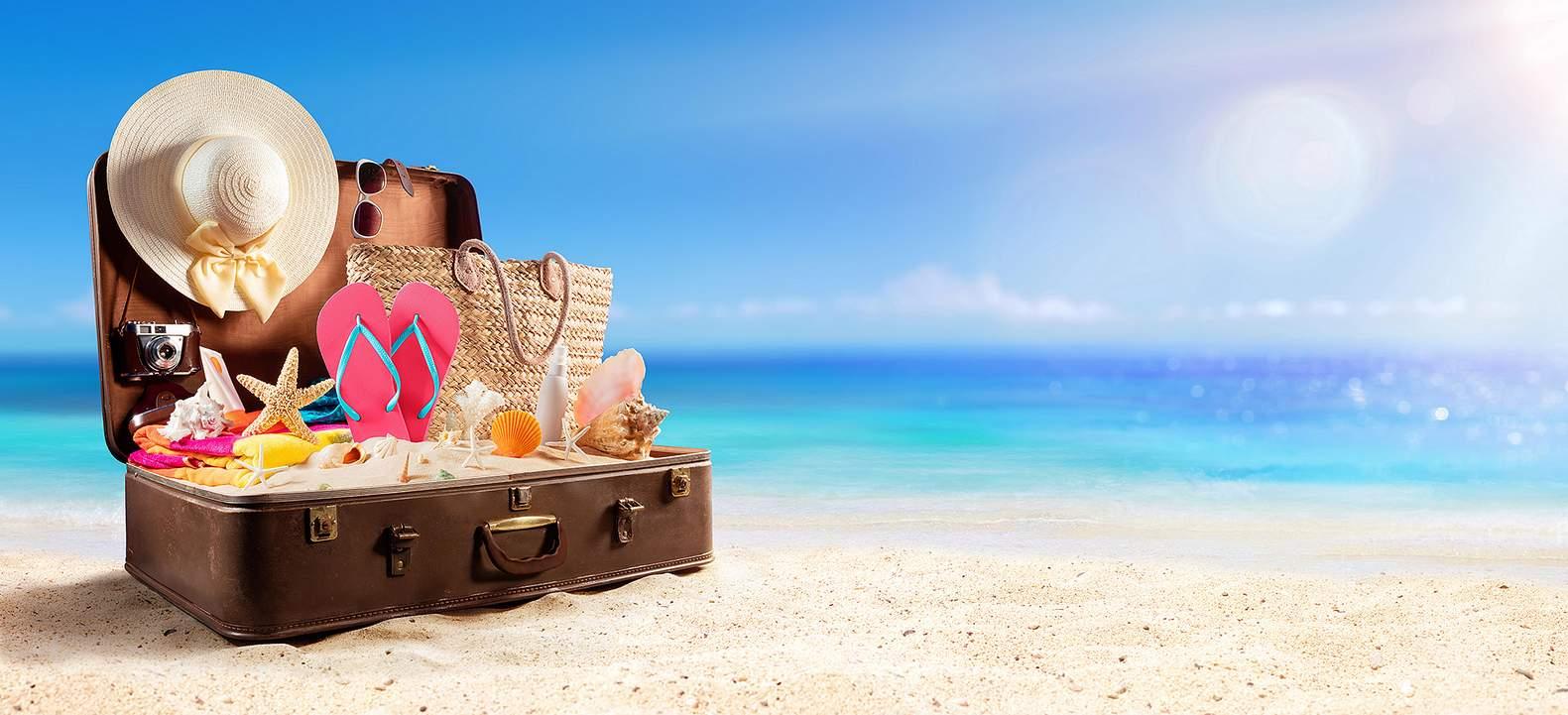 Foto ilustrativa - Uma mala aberta com itens usados para ir à praia. No fundo uma foto desfocada de uma praia