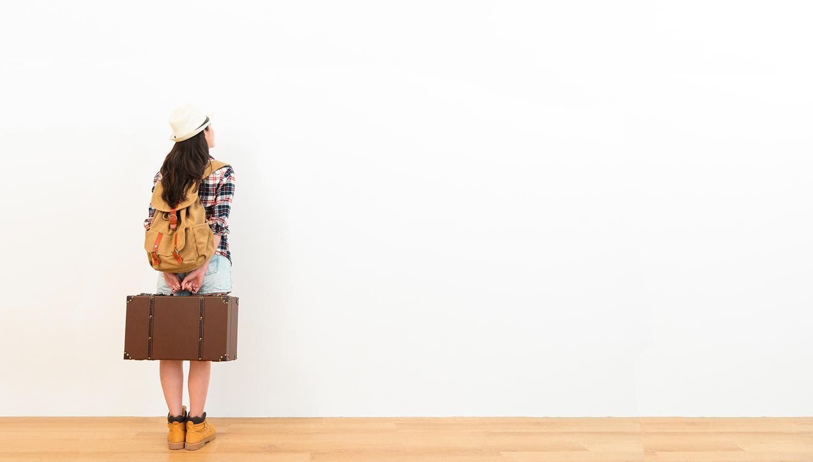 Foto Ilustração - Uma mulher de costas com mochila e mala, pronta para viagem.