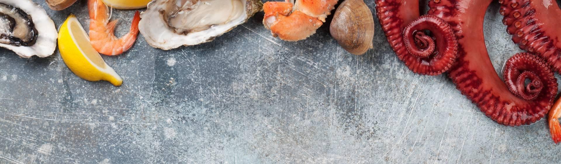 Foto de uma mesa com camarão, polvo, conchas e alguns outros frutos do mar